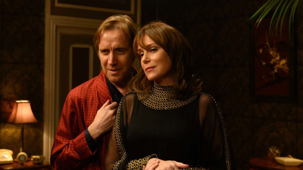 Rhys Ifans as Eric Morley and Keeley Hawes as Julia Morley in Misbehaviour, directed by Philippa Lowthorpe. Photo: Parisa Taghizadeh. Copyright: Pathe Productions Ltd. All Rights Reserved.